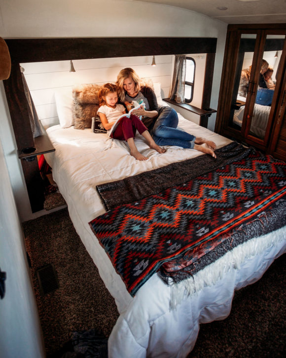mother and daughter read a bedtime story from a bed in a large RV trailer rental.