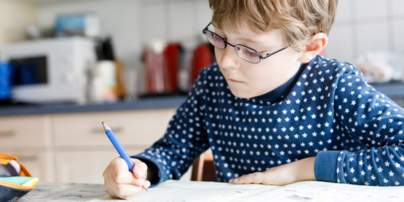 white boy with glasses sitting at a kitchen table to write