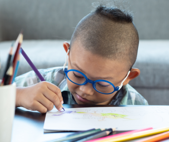 young child with glasses draws a comic book page to practice writing skills