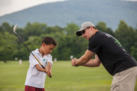 a camp counselor and young golfer work together at this sleepaway golf camp.
