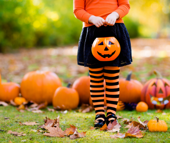 A little girl stands in the grass with pumpkins holding a pumpkin for trick or treating in New Jersey
