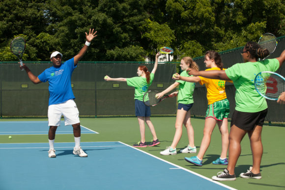 A world sports camp counselor works with girls in the sleepaway tennis camp.