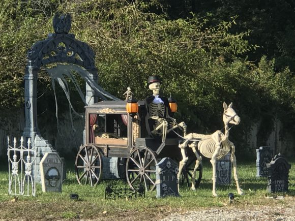 Outdoor Halloween decorations including a skeleton driving a stagecoach pulled by a skeleton of a horse going through a graveyard.