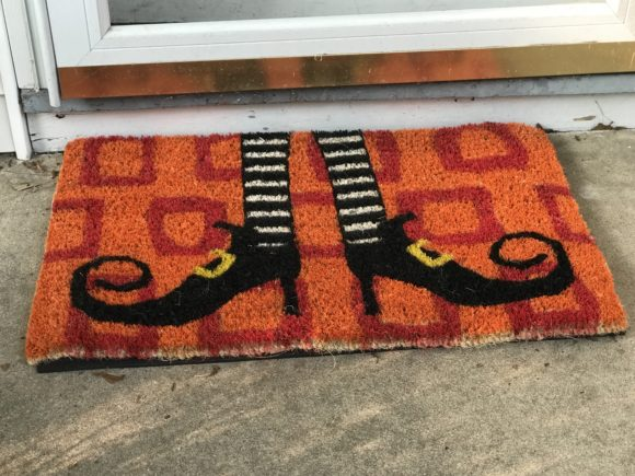 The Olive & Cocoa Witch's Legs Door Mat makes a great easy element for outdoor Halloween decor on a front porch.