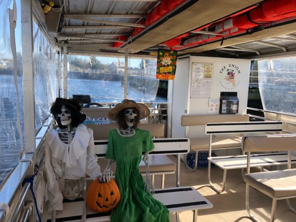 Two dressed skeletons sit on the Pohatcong II for a Halloween boat ride with the Tuckerton Seaport, it's one of the best New Jersey Halloween activities.