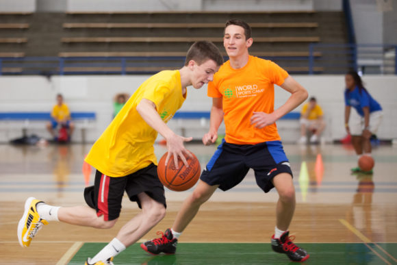 two teens play basketball as part of an overnight basketball camp offered by World Sports Camp.