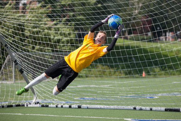 a goalie catches a soccer ball in the net as part of this overnight soccer camp.