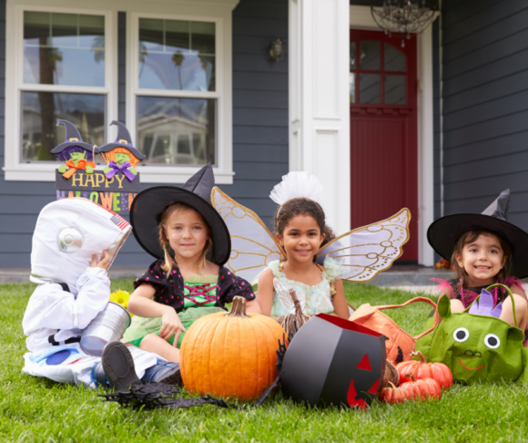 a group of NJ kids sit on a lawn in Halloween costumes ready to go trick or treating
