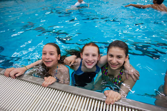 a group of female world sports campers swim in the pool.