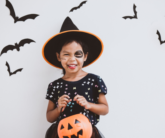 a little girl dressed like a witch is ready for NJ trick or treating