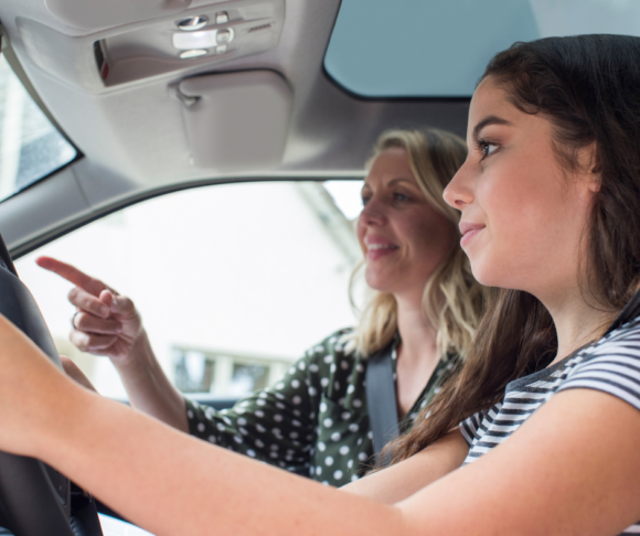 mother and daughter are in a car, mom is teaching daughter to drive