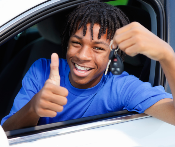 black male teenager sits in a car giving a thumbs up and holding a set of keys.
