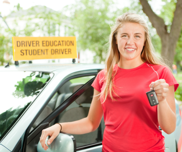 female stands in front of a car as part of earning driving hours for getting a Driver's License in New Jersey
