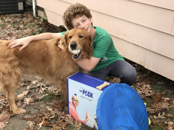 golden retriever and boy pose together with The Pack gift box.