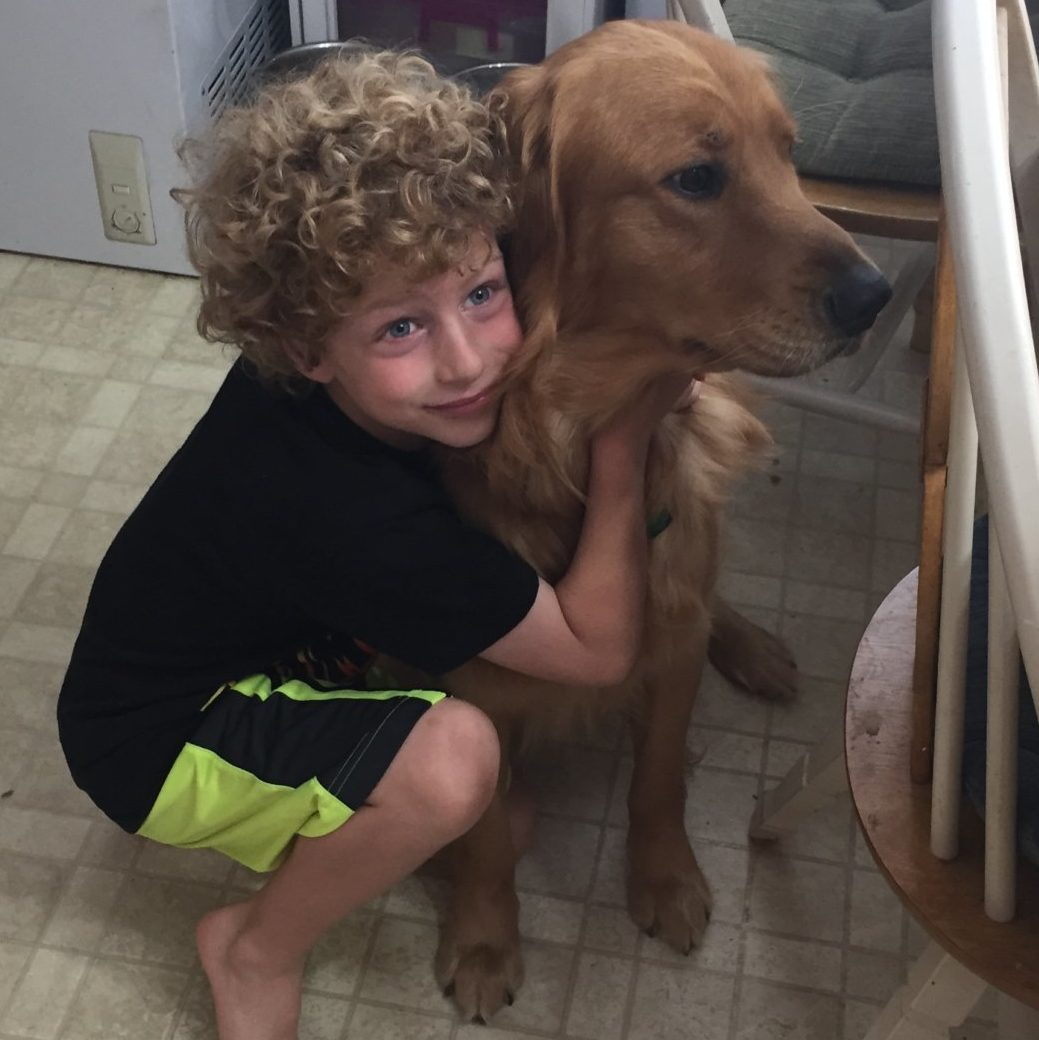 a little boy hugs his golden retriever.