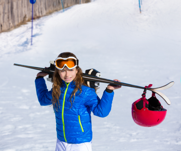 girl holding ski equipment over her shoulders