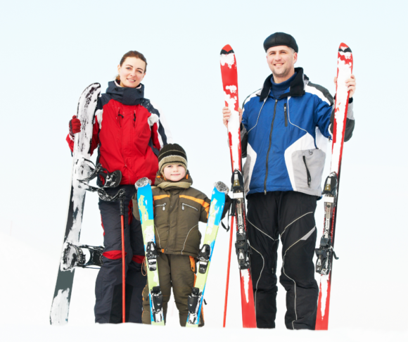 a family stands together holding ski equipment