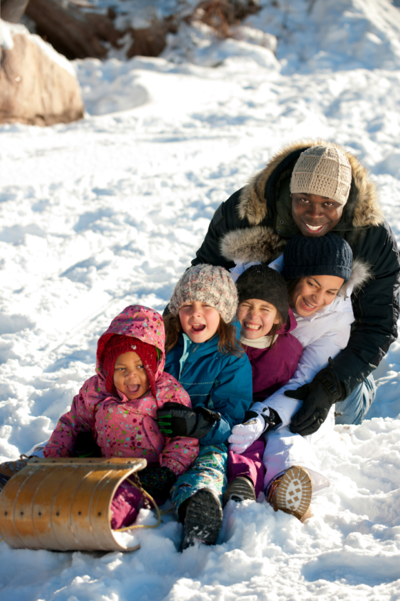 a couple with 3 children sledding in New Jersey