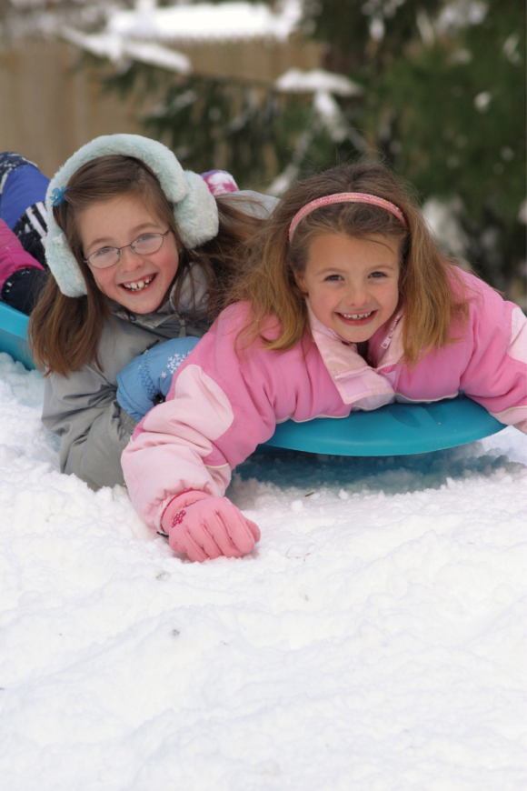 2 girls sledding down a hill in New Jersey