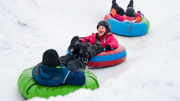 3 kids in snowtubes on a sledding hill in New Jersey