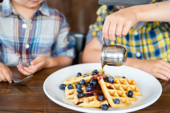 Gluten free waffles made with Josie's Best Gluten Free Mixes drizzled with maple syrup