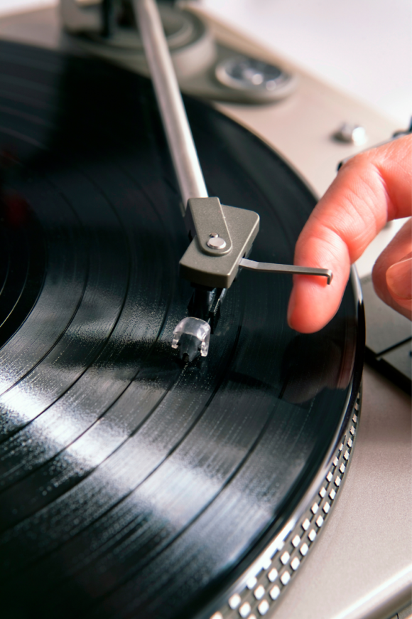 a person picks up the needle on a record player