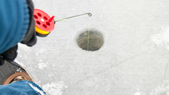 an ice fisher lowers the fishing line through a hole in the ice