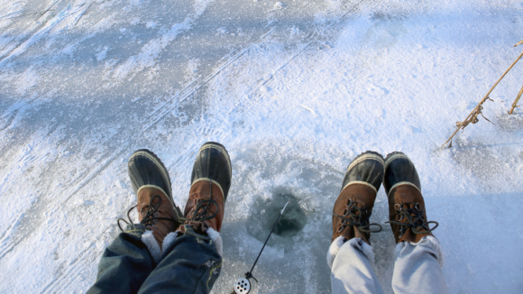 two sets of feet waiting next to an ice fishing spot in New Jersey.