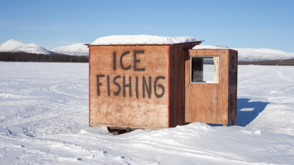 an ice fishing house sits on a stretch of snow.