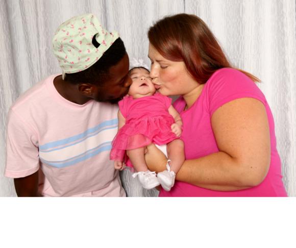 Family bonding time biracial couple embraces their newborn