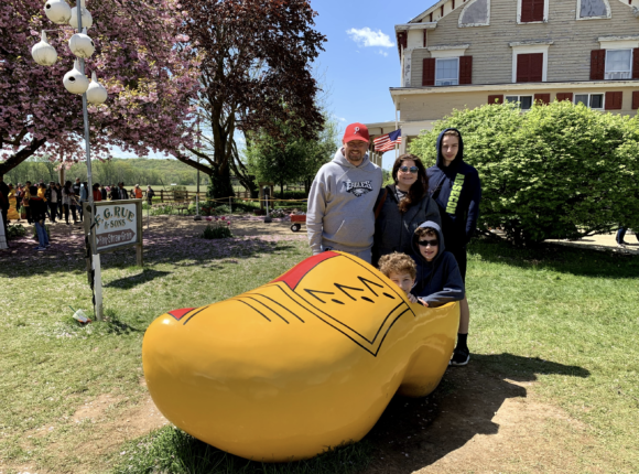 Family poses with a very large dutch wooden shoe at Holland Ridge tulip farm in nj