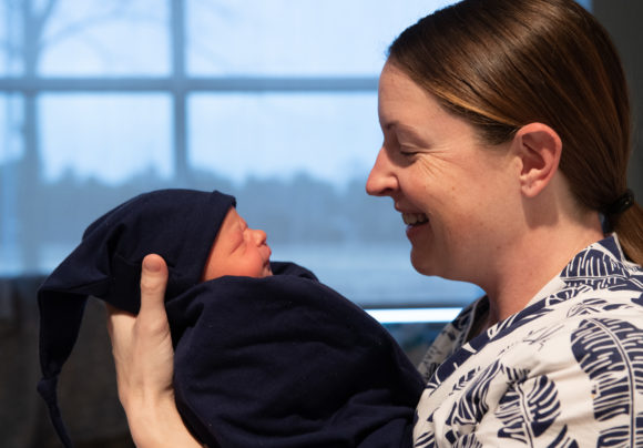 A new mom with her baby. She recognizes her body changes after pregnancy and she's taking time to enjoy her baby.