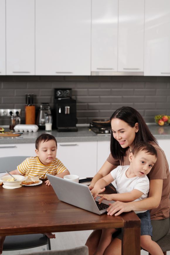 Mom on laptop with kids