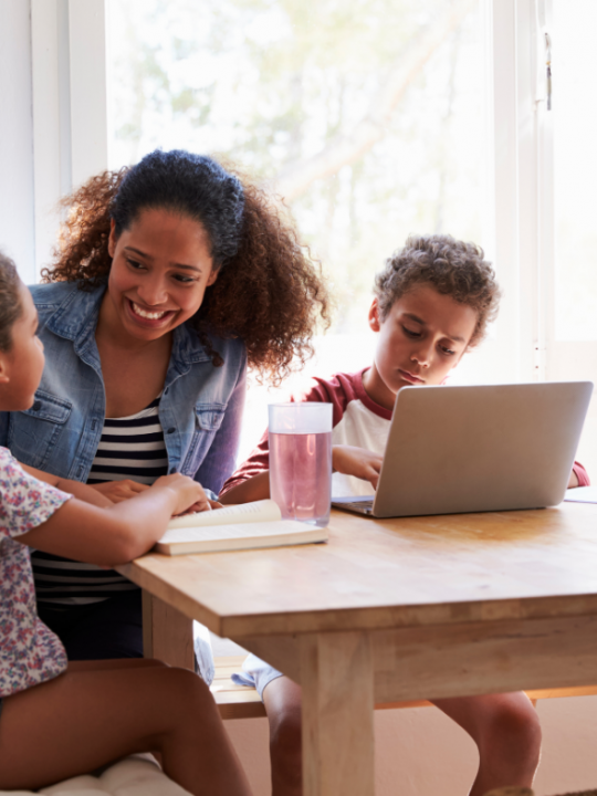 A contributor Mum Sitting with Kids at Kitchen Table, Son Using Laptop