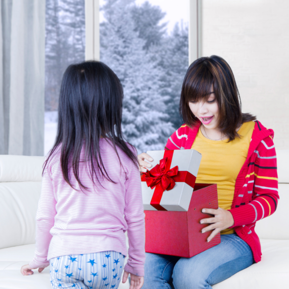 An asian mother being surprised with a gift from her asian daughter.png