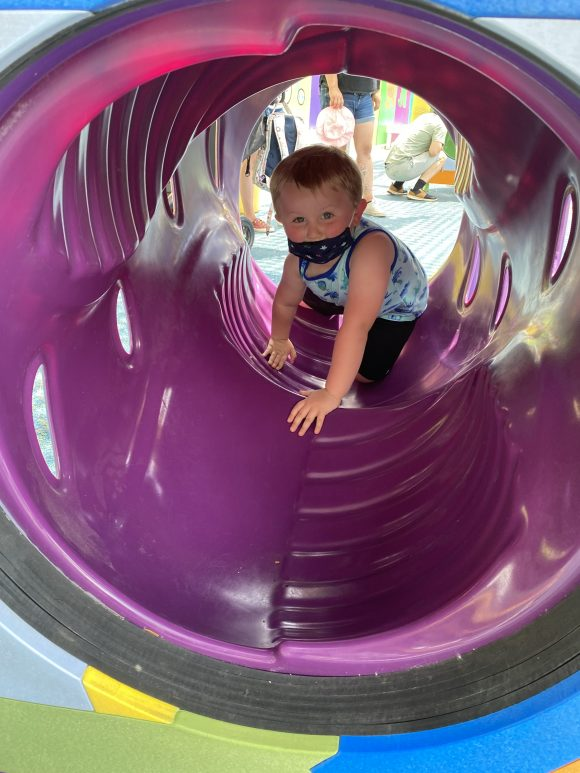 A toddler crawls through a tube in the Mini Monster Clubhouse at Sesame Place.