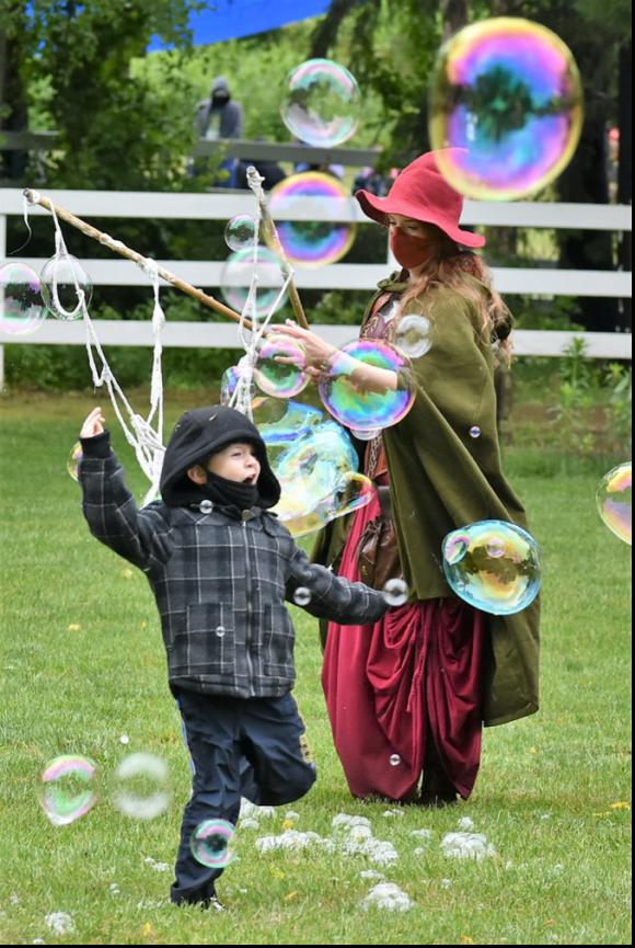 A child dances through bubbles from the bubble magician at the NJ Renaissance Faire