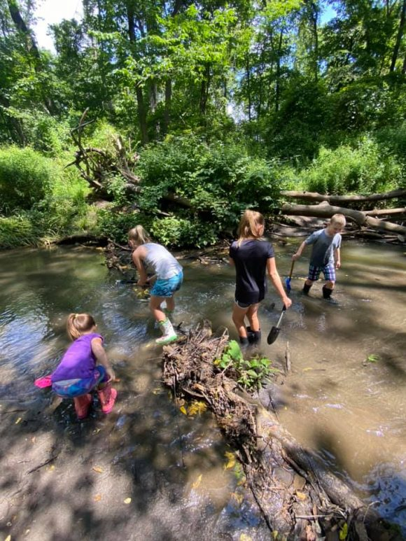 kids walking in rain boots in a stream at Big Brook Preserve