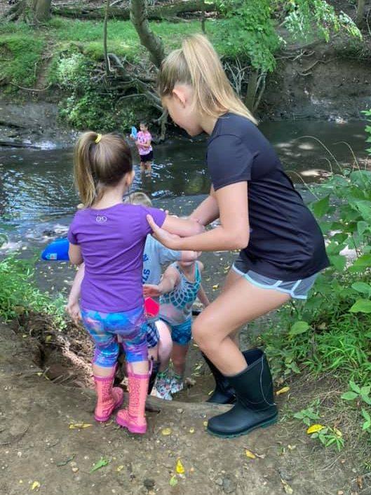 Big Brook Preserve Bis sister helps little sister at the river bed