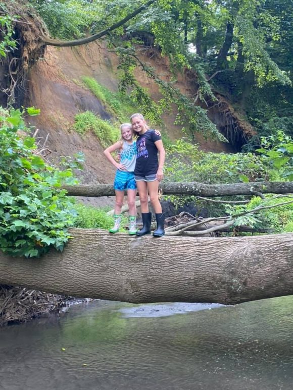 Big Brook Preserve sisters pose for picture on tree trunk across stream