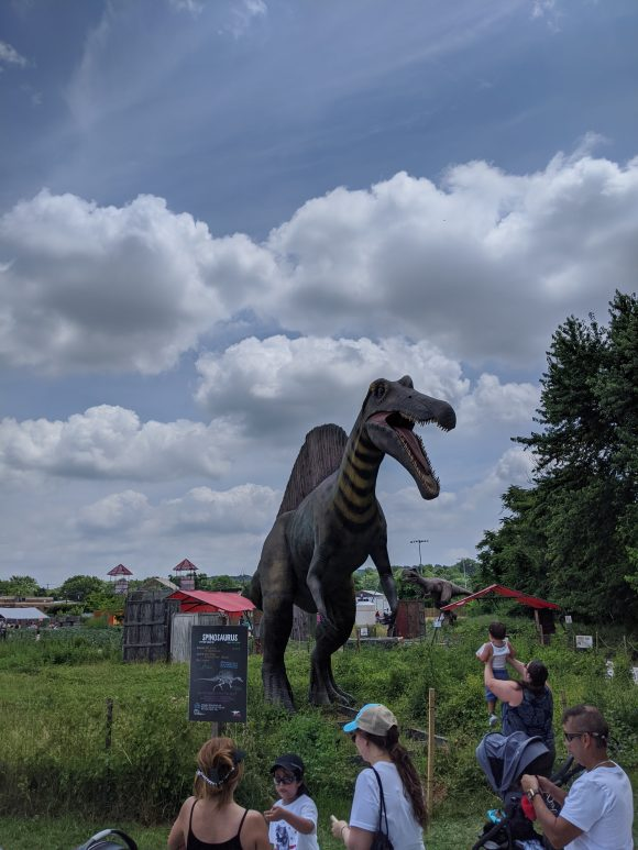 A woman holds up a toddler at Field Station Dinosaur to see the Spinosaurus.
