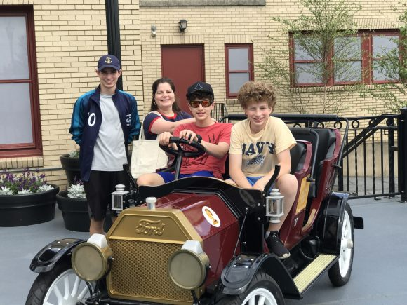 family picture on classic car at The Chocolatier at Hershey Chocolatetown