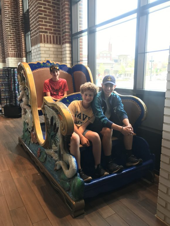 picture of teen boys in carrousel seat inside Hershey Supply Company in Chocolatetown