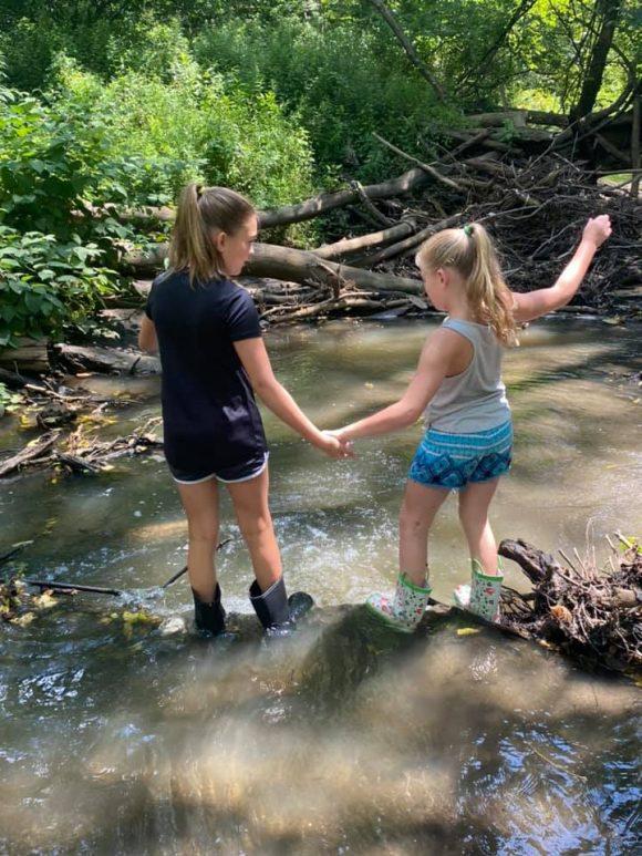 sisters walk through a stream at Big Brook Preserve in nj