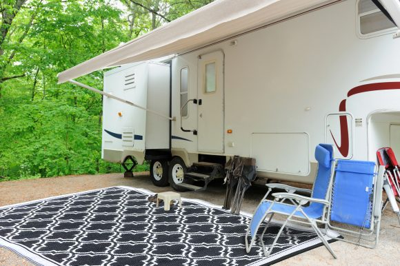 Recreational vehicle fifth wheel travel trailer in wooded campsite with awning and folding chairs.