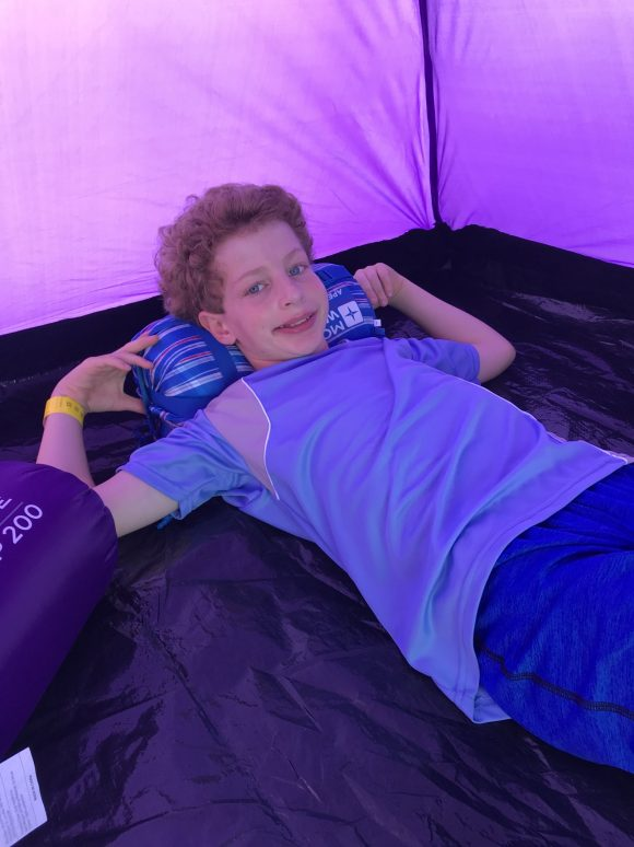 Boy laying in tent using a sleeping bag as a pillow
