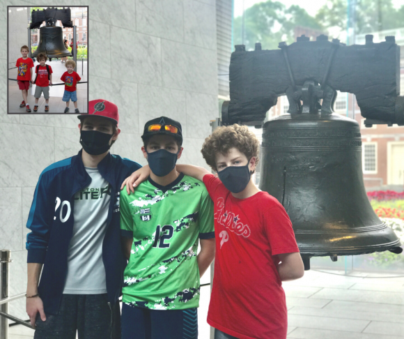 Boys posed with the Liberty Bell in Philadelphia during a Philly staycation with kids