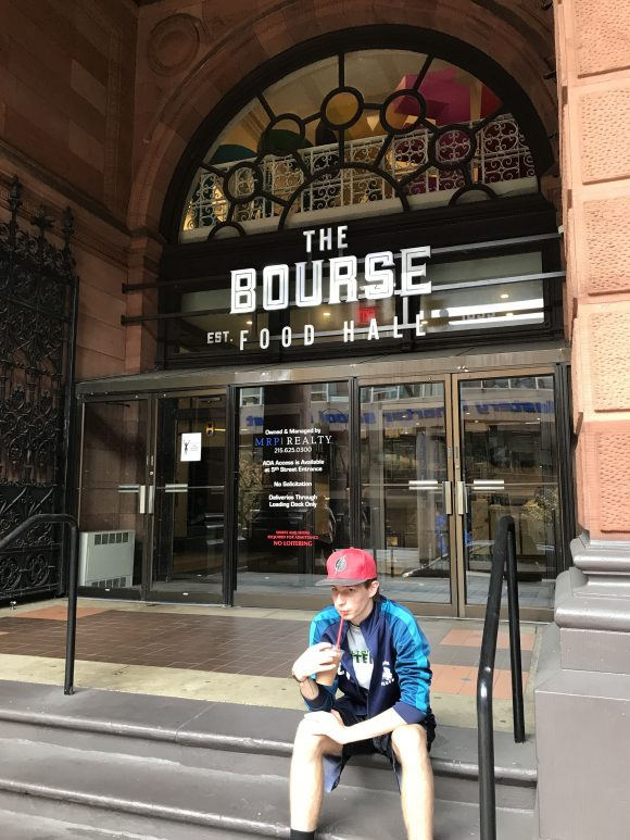 Teen sits on the steps of the Bourse in Philadelphia a place to eat with kids
