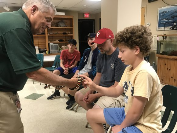 family takes turn touching a snake at the ZooAmerica behind the scenes tour.