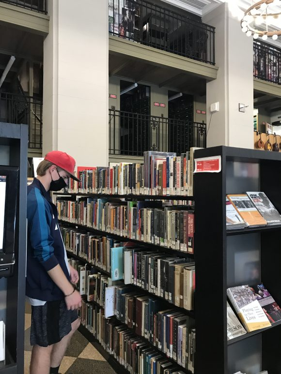 teen peruses the collection of books at The Free Library of Philadelphia - Parkway Central Library